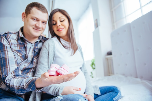 Donna incinta e suo marito tenendo stivaletti