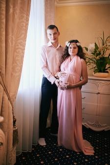 Donna incinta e uomo in posa in un interno classico in attesa di un bambino