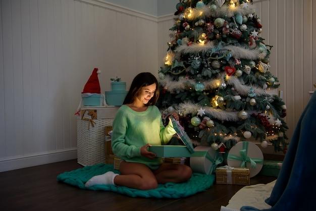 Donna incinta felice a casa vicino all'albero di natale durante la celebrazione di natale