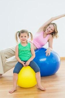 Donna incinta felice che si esercita sulla sfera di esercitazione con la giovane figlia