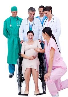 Donna incinta graziosa che si siede sulla sedia a rotelle e su un gruppo di medici