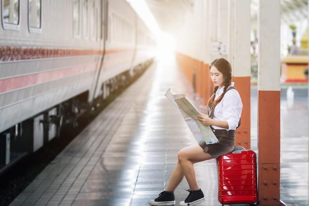 Donna incinta in abito rosso che trasportano bagagli rossi e guardare la mappa al viaggio stazione ferroviaria.