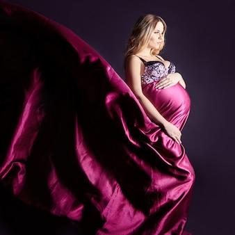 Donna incinta in lingerie su sfondo grigio