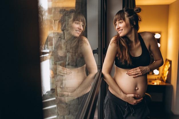 Donna incinta in piedi vicino alla finestra