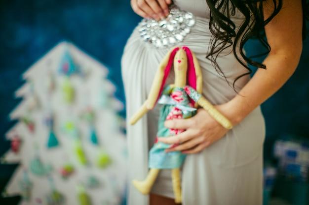 Donna incinta in possesso di un giocattolo carino sul suo ventre