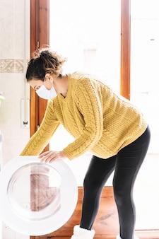 Donna incinta in un maglione giallo che indossa una maschera in faccia per prevenire i virus mentre sta caricando una lavatrice