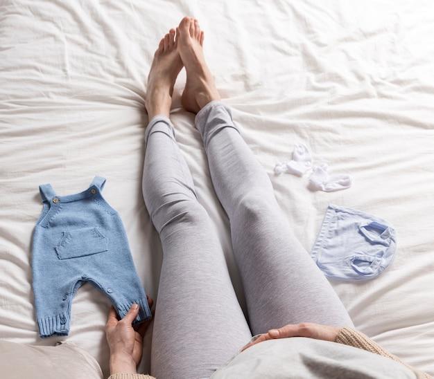 Donna incinta laica piatta con vestiti per bambini