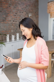 Donna incinta sorridente che esamina smartphone a casa