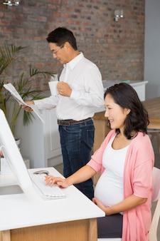Donna incinta sorridente che per mezzo del computer portatile a casa mentre il suo marito sta leggendo il giornale
