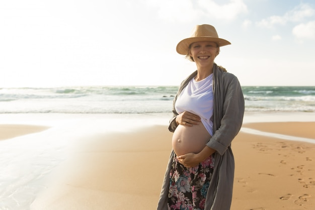 Donna incinta sorridente felice che si tiene per mano sulla pancia