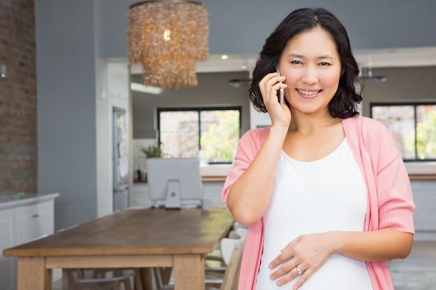 Donna incinta sorridente su una telefonata a casa