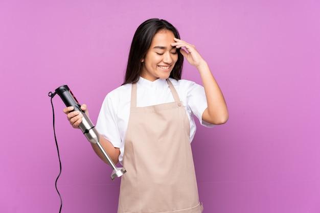 Donna indiana che per mezzo del miscelatore della mano sulla risata viola della parete