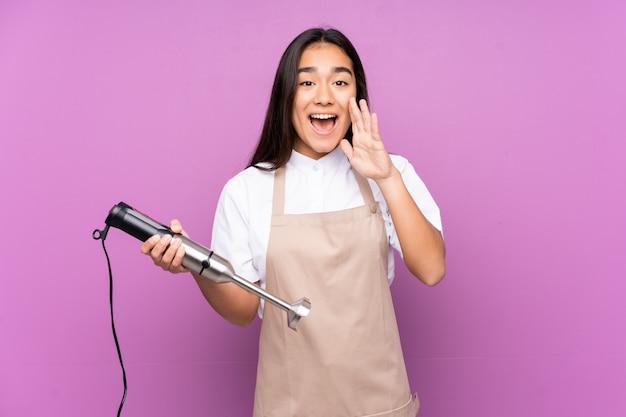 Donna indiana che usando il miscelatore della mano isolato sulla parete viola che grida con la bocca spalancata
