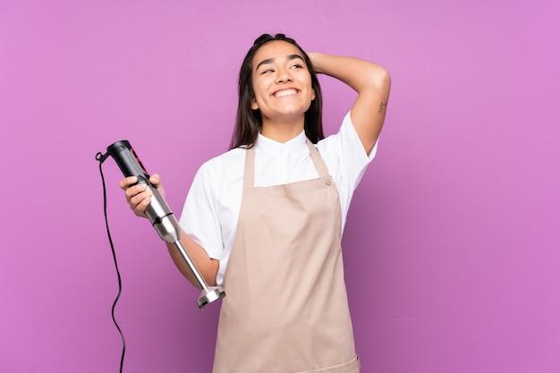 Donna indiana che usando il miscelatore della mano isolato sulla risata viola della parete