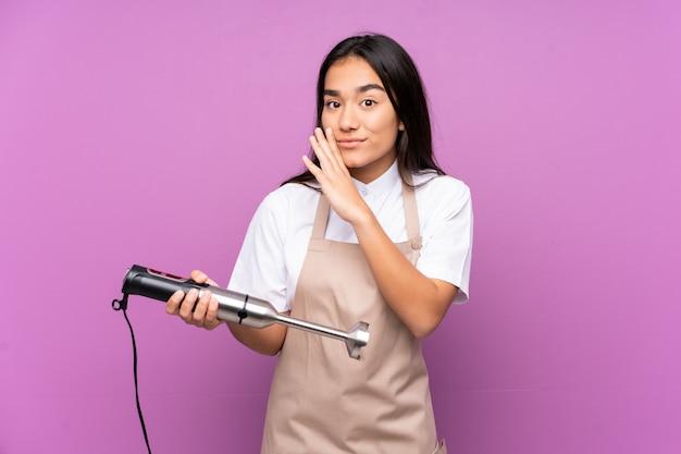 Donna indiana che usando il miscelatore della mano sulla parete viola che bisbiglia qualcosa