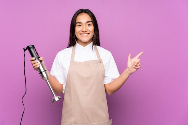 Donna indiana che usando il miscelatore della mano sulla parete viola che indica barretta il lato