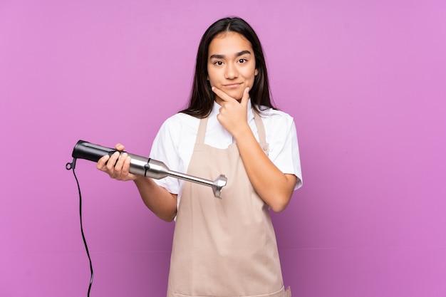 Donna indiana che usando il miscelatore della mano sulla parete viola che pensa un'idea