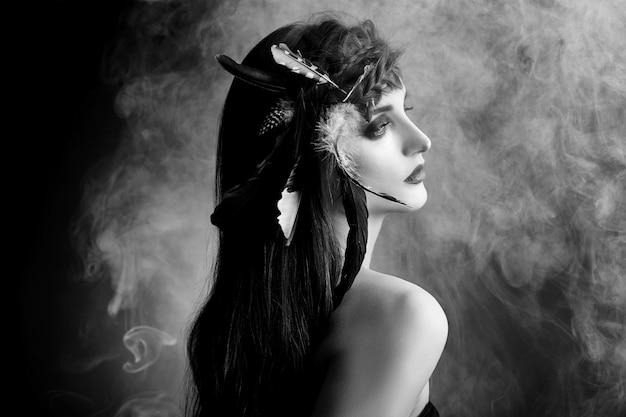 Donna indiana con piume tra i capelli, ritratto di bellezza donna indiana americana in fumo. bel viso con pelle pulita, trucco a contrasto