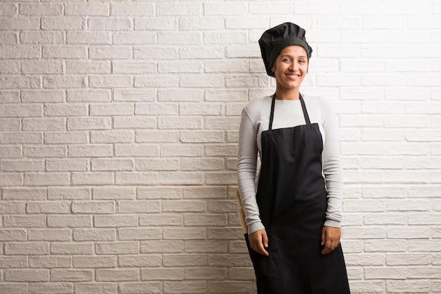 Donna indiana giovane panettiere contro un muro di mattoni allegro e con un grande sorriso