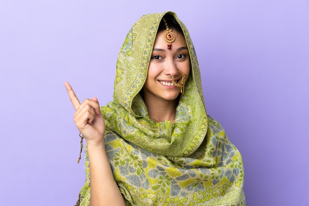 Donna indiana isolata su sfondo viola felice e rivolto verso l'alto