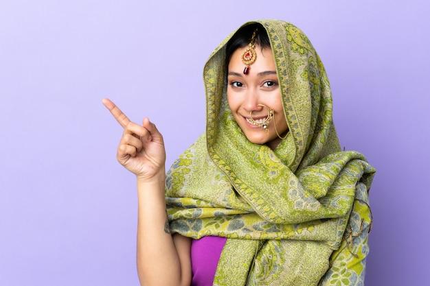 Donna indiana isolata sul dito indicante porpora al lato