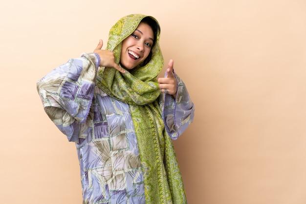 Donna indiana isolata sulla parete beige che fa gesto del telefono e che indica parte anteriore