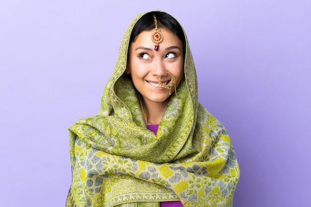 Donna indiana isolata sulla porpora che ha dubbi mentre osservando in su