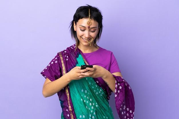 Donna indiana isolata sulla porpora che invia un messaggio con il cellulare