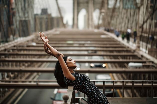 Donna indiana splendida e tenera in vestito nero che posa prima del ponte di brooklyn