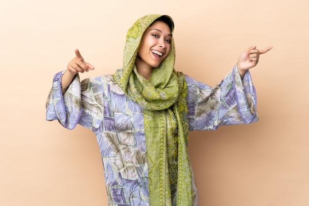 Donna indiana sulla parete beige che indica barretta ai laterali e felice