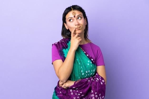 Donna indiana sulla parete viola che ha dubbi mentre osserva in su