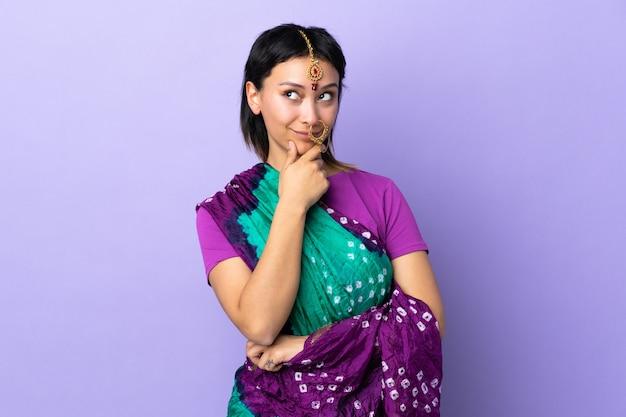 Donna indiana sulla parete viola che pensa un'idea mentre osservando in su