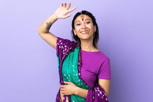 Donna indiana sulla parete viola che saluta con la mano con l'espressione felice