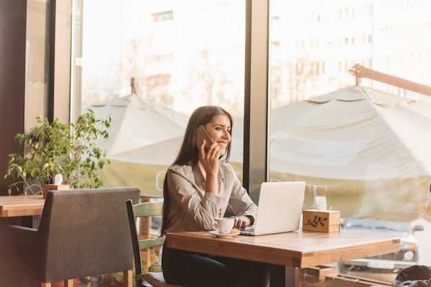 Donna indipendente che lavora con il computer portatile in caffetteria
