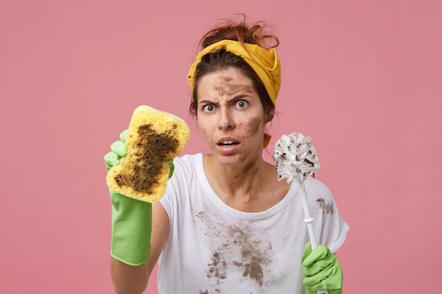 Donna infastidita con la faccia sporca che tiene la spugna e il pennello nelle mani di cattivo umore