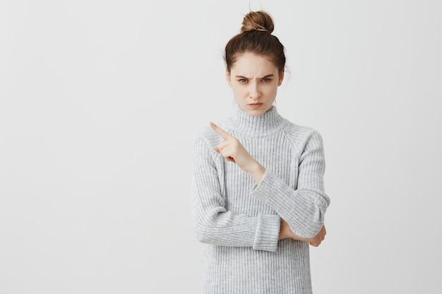 Donna infastidita e arrabbiata che esprime antipatia con il gesto. cattivo atteggiamento femminile verso qualcosa che punta il dito su di esso.