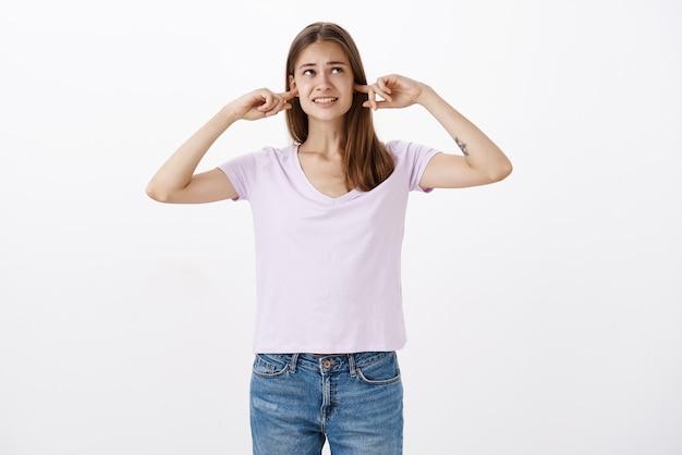Donna infastidita intensa dispiaciuta con tatuaggio che stringe i denti chiudendo le orecchie con il dito indice guardando l'angolo in alto a destra interrotto con un suono forte