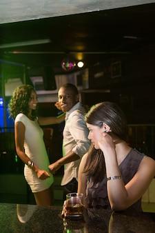 Donna infelice che esamina una coppia che balla dietro lei nella barra