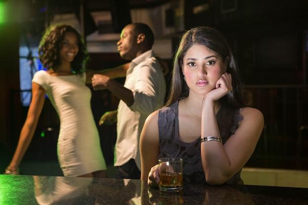 Donna infelice che si siede al bancone del bar e coppia che balla dietro di lei nel bar
