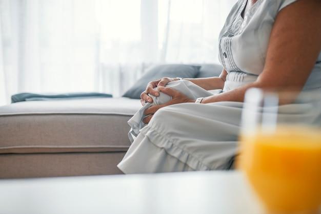 Donna infelice che soffre dal dolore nella gamba a casa