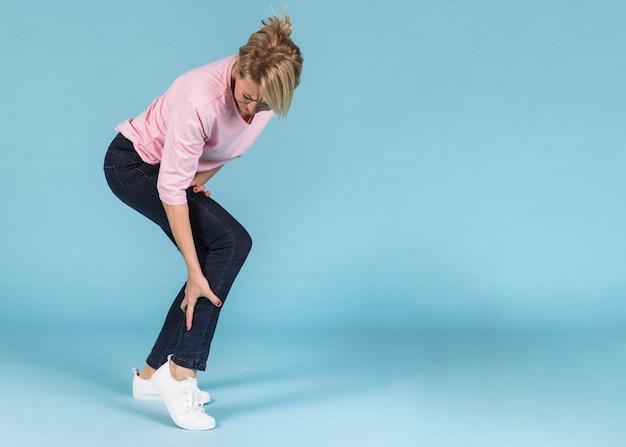 Donna infelice che soffre di forti dolori alla gamba