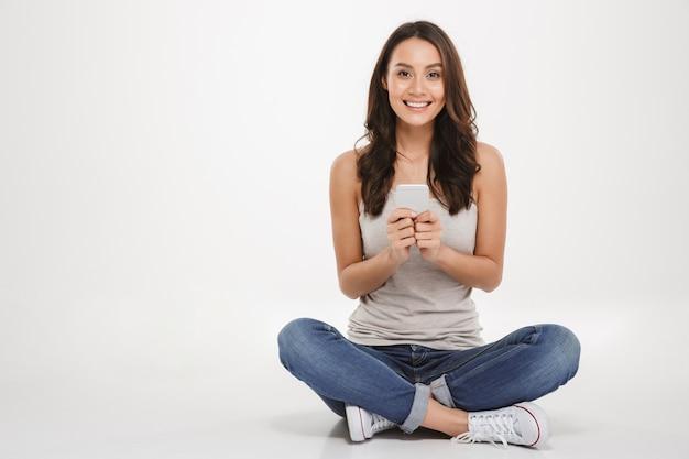 Donna intelligente con lunghi capelli castani seduto con le gambe incrociate sul pavimento utilizzando smartphone argento e guardando la fotocamera, isolata su un muro bianco