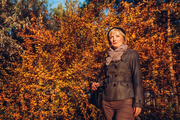Donna invecchiata centrale che cammina nella foresta di autunno che indossa l'attrezzatura alla moda di caduta con gli accessori