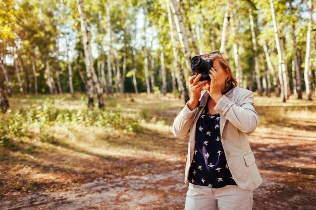 Donna invecchiata centrale che cattura le immagini con la macchina fotografica in foresta