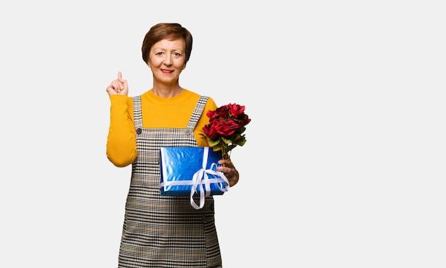 Donna invecchiata centrale che celebra il giorno di biglietti di s. valentino che indica il lato con il dito