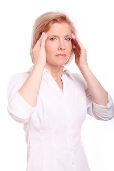 Donna invecchiata centrale che ha dolore alla testa sopra fondo bianco