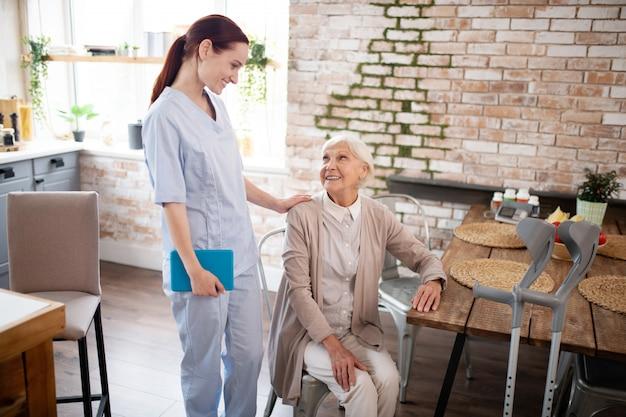 Donna invecchiata che parla con sua infermiera diligente utile