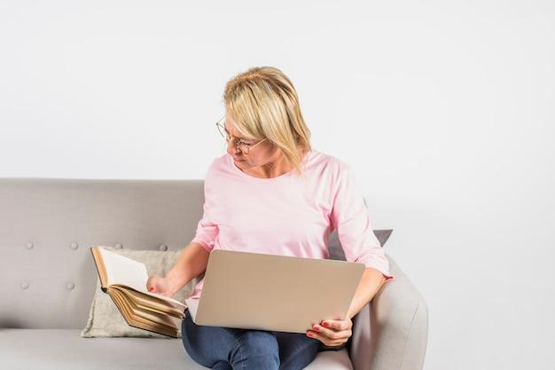 Donna invecchiata in camicia rosa con laptop e libro sul divano