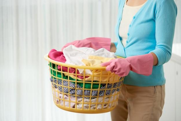 Donna irriconoscibile potata che fa lavanderia che tiene il canestro di tela