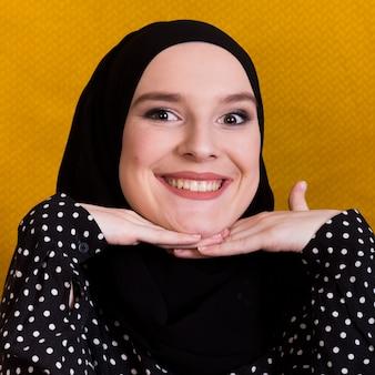 Donna islamica sorridente graziosa che esamina macchina fotografica